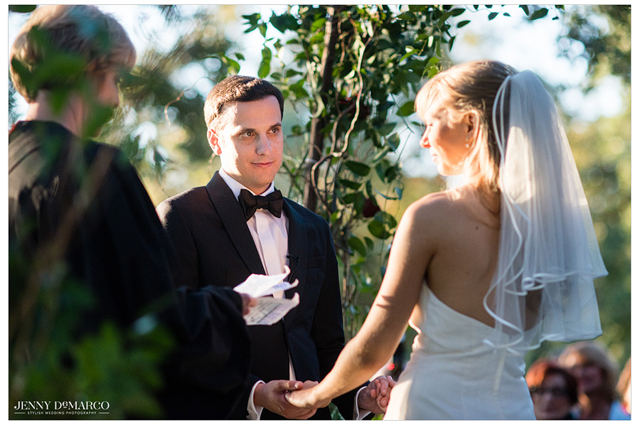 Loving picture of groom looking at his bride while they exchange vows during their outdoor wedding.