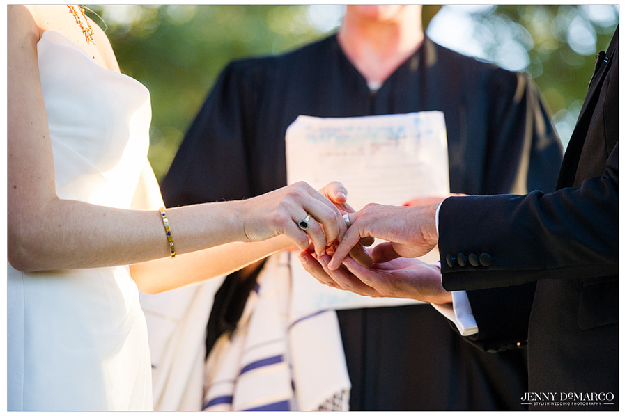 Bride and groom exchange the rings during their wedding ceremony at Vineyards at Chappel Lodge.