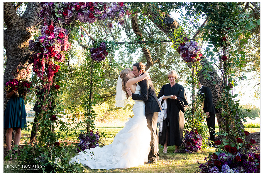 Bride and groom share a kiss during their vineyard wedding ceremony.