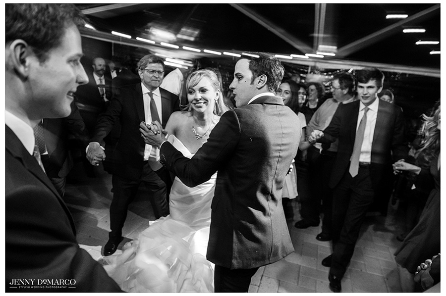 Black and white photo of bride and groom dancing a traditional Polish dance at their wedding.