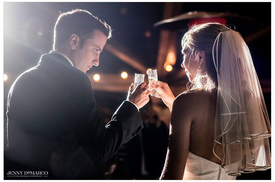 Bride and groom cheers before taking a vodka shot at their Polish wedding reception.
