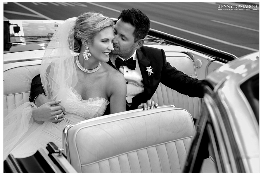 The groom kisses the bride on the cheek as they climb into the vintage cadillac to head to the reception.