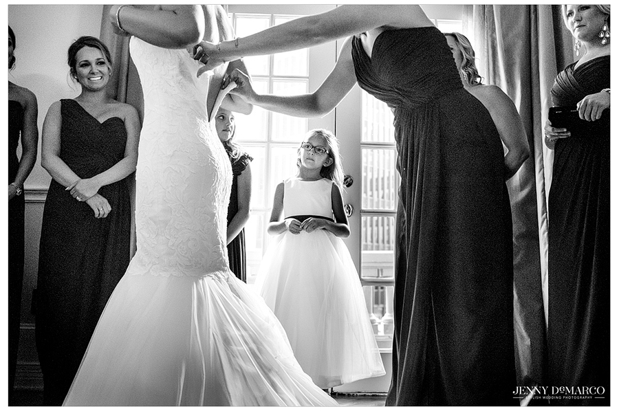 The maid of honor helps the bride zip up her dress as the flower girl admiringly looks on.