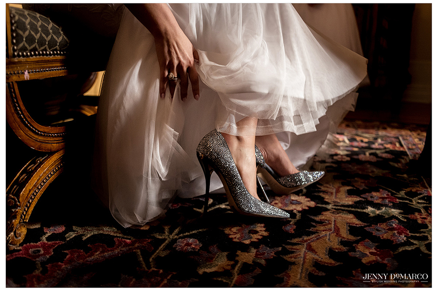 The bride slips into her sparkly heels as she puts the finishing touches on her look.