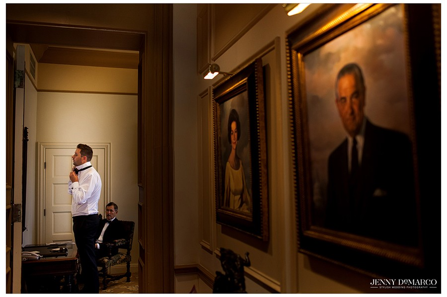Surrounded by historical portraits at the Driskill, the groom ties his bow-tie in preparation for the big day.