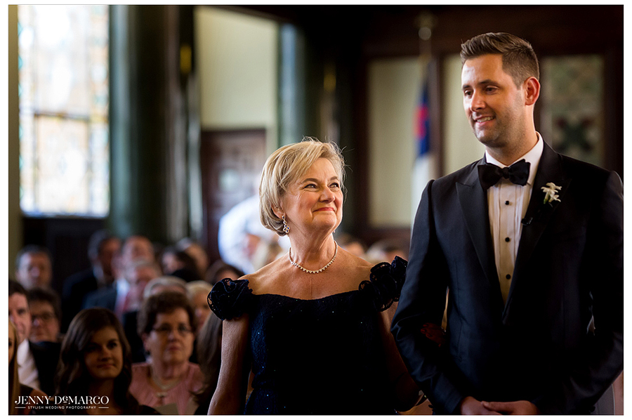 The grooms mother looks up lovingly at her son as they walk down the aisle.
