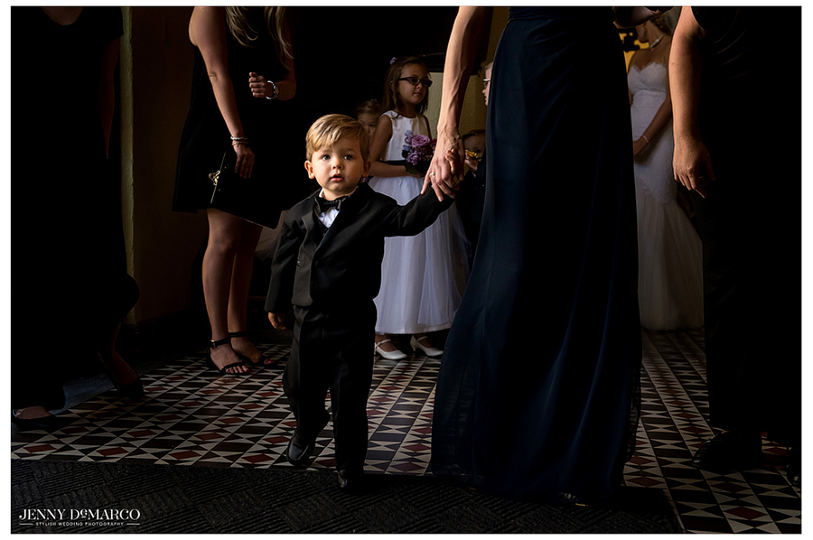 The adorable ring bearer patiently waits to walk down the aisle as the ceremony begins.