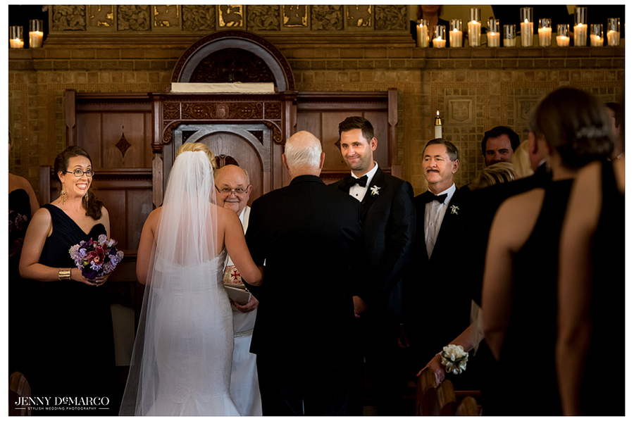 The groom lovingly watches his beautiful bride walk down the aisle.