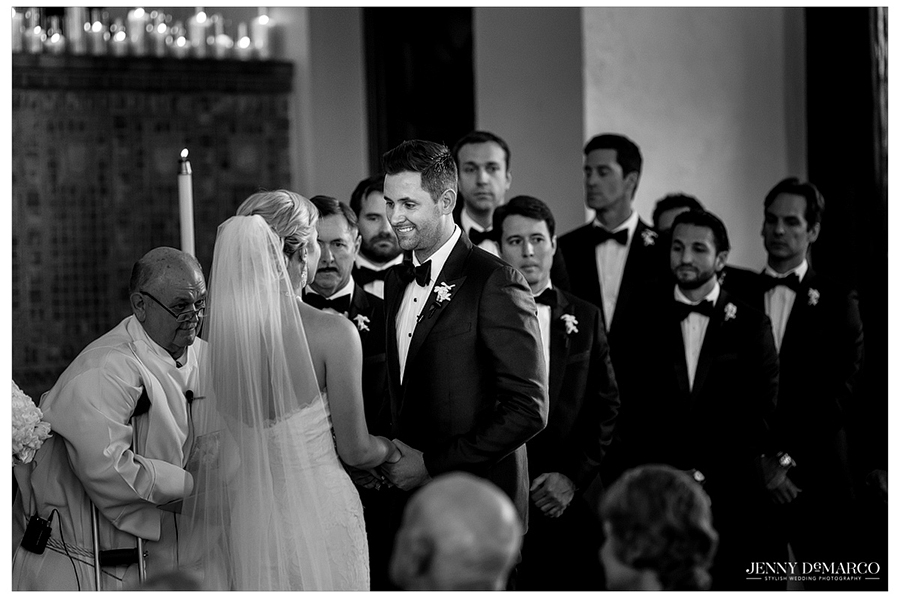The bride and groom hold hands and look into each other's eyes as they recite their vows.