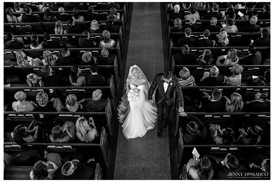 The groom fist bumps a close friend sitting in the pew as he and his new wife walk down the aisle.