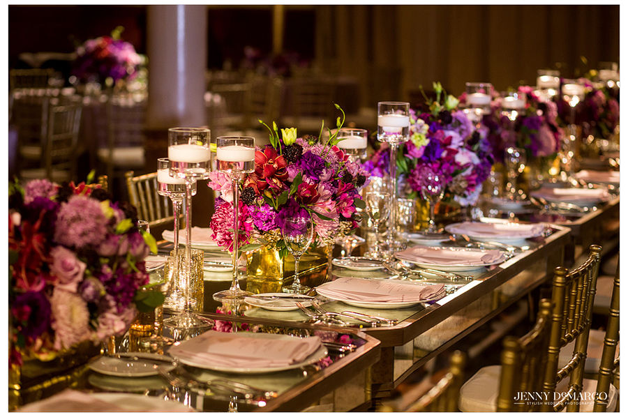 Purple and pink flowers line the center of the gold mirrored table for the wedding party.
