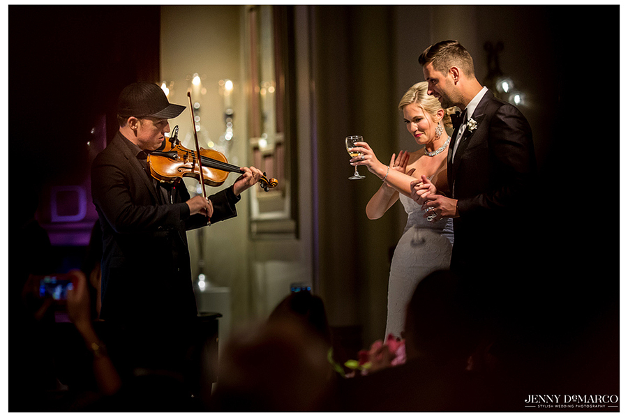 The bride and groom clap along to a violist performing on stage.