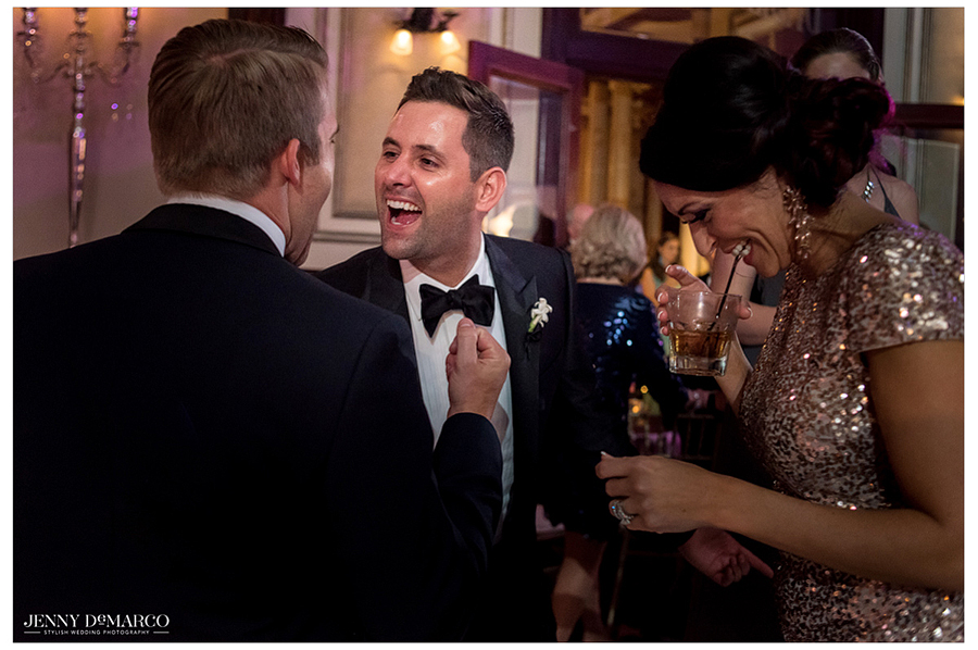 The groom greets his guests, sharing a laugh with friends on the dance floor as the music kicks up.