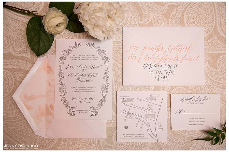 The elegant, floral wedding invitations are on display along with a few white flowers.