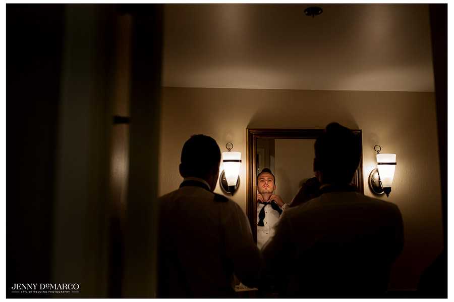 The groom ties his bowtie in the mirror with his best man at his side.