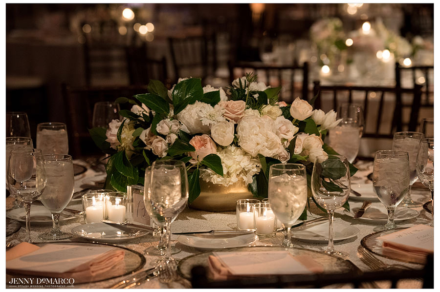 Soft, neutral flowers and candles act as beautiful centerpieces at the guest tables.
