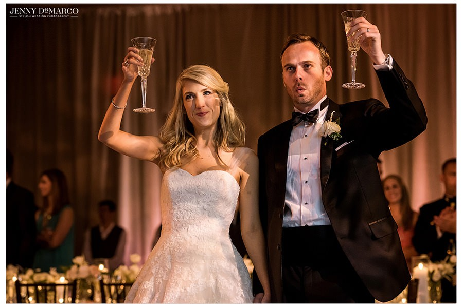 The bride and groom raise their glasses as family and friends begin their toasts.