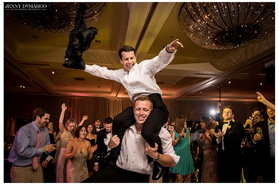 A friend hops on the shoulders of another guest for a picture as the reception draws to a close.