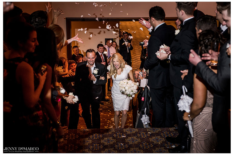 Family and friends surround the bride and groom as they exit the reception hall, throwing flowers in their path.