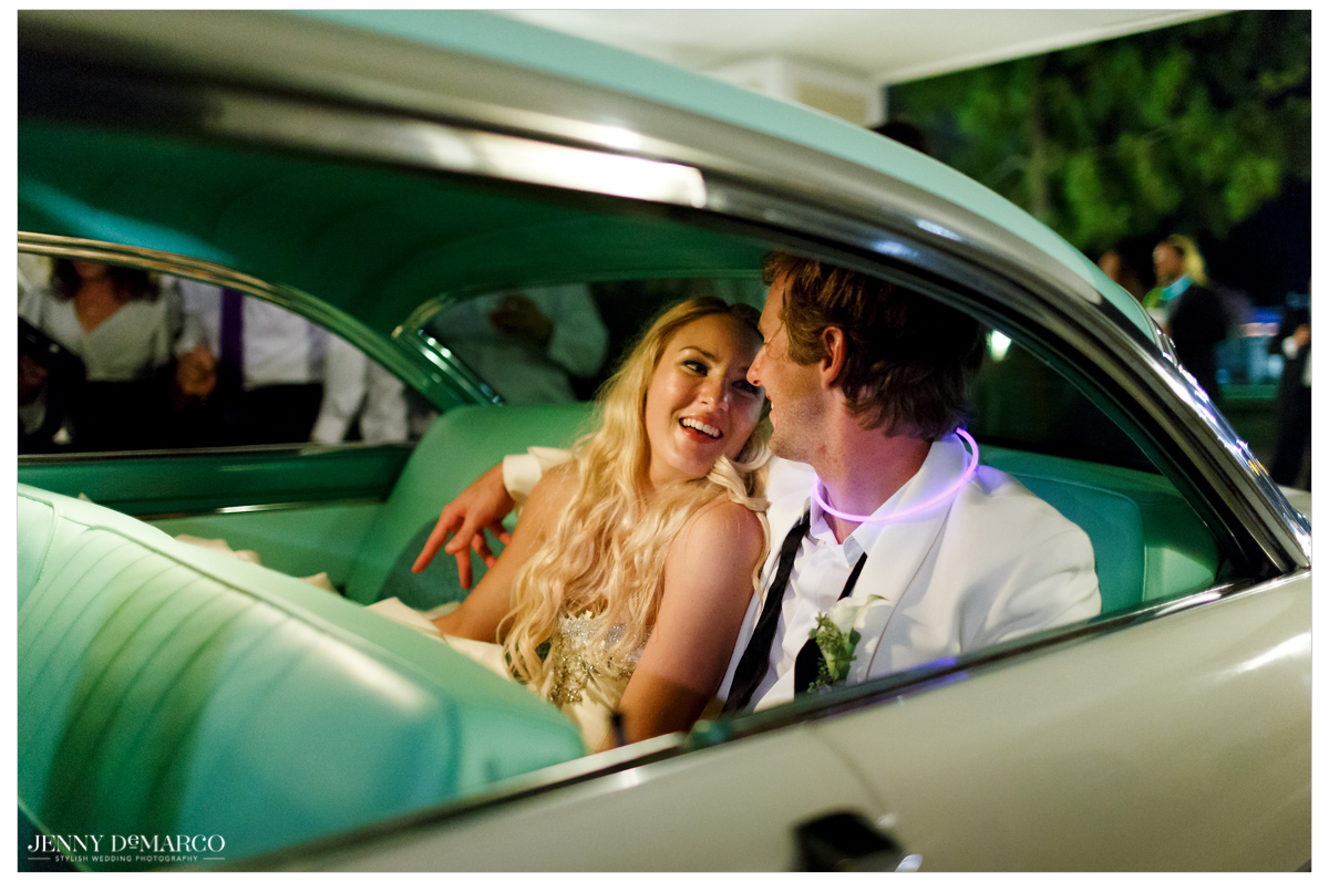 The bride and groom jump in their getaway car as they leave the reception.