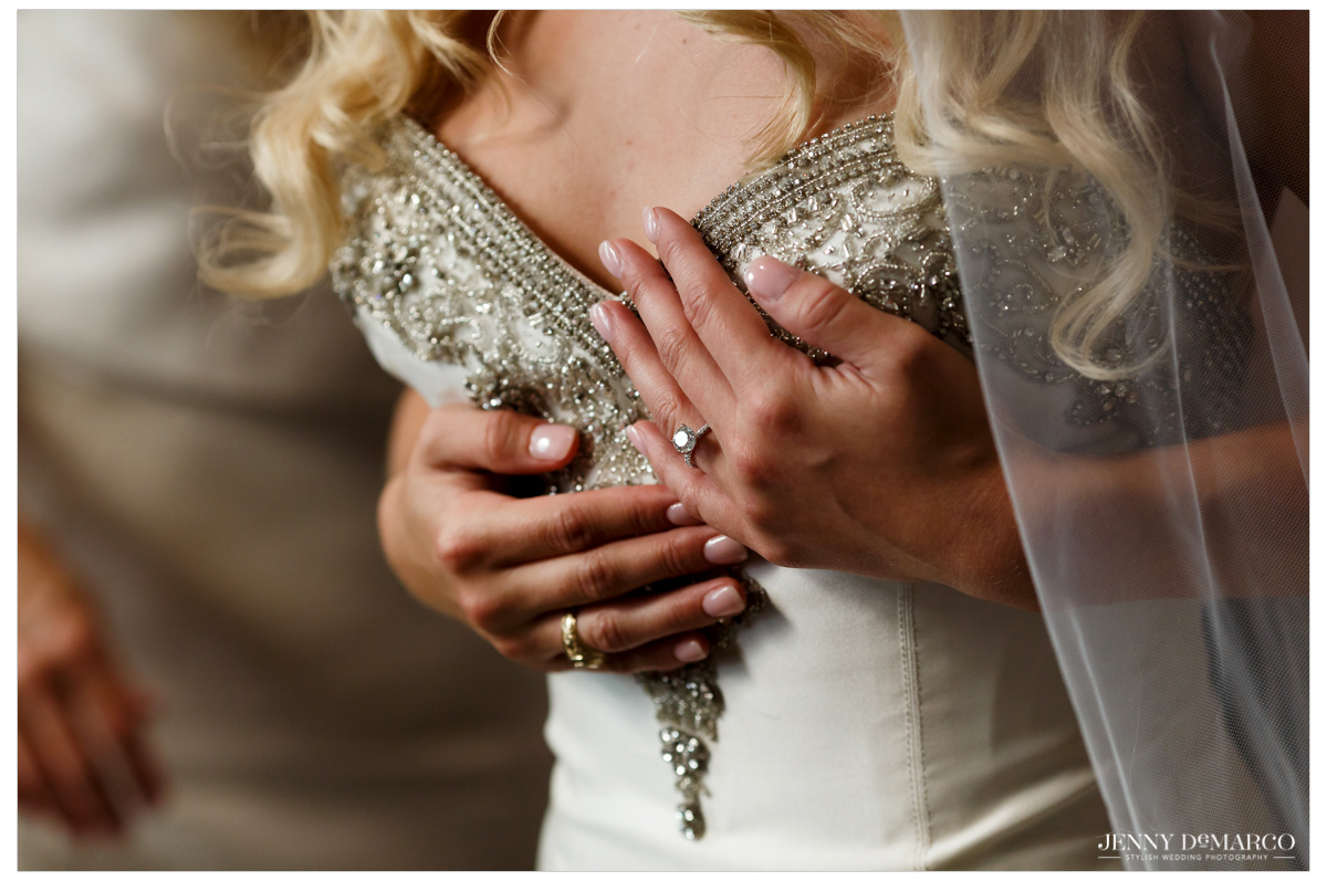 The bride displays her engagement ring against her dress.