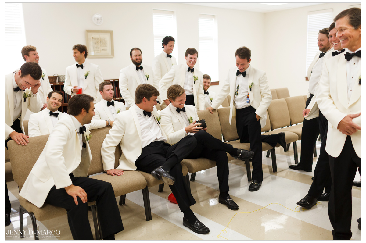 The groom and groomsmen hang out as they put the final touches on their look.