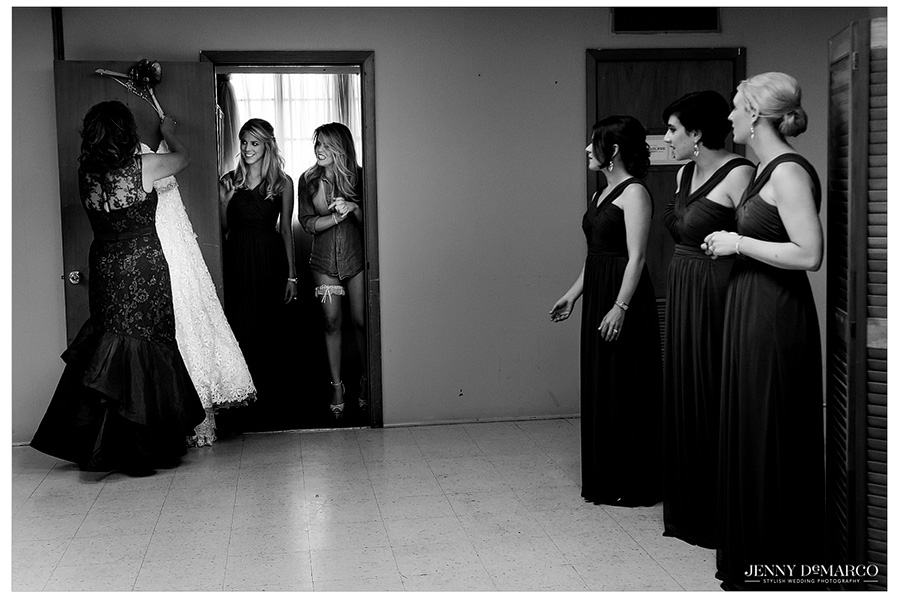 Bridesmaids watch as the bride prepares to put on her wedding dress.