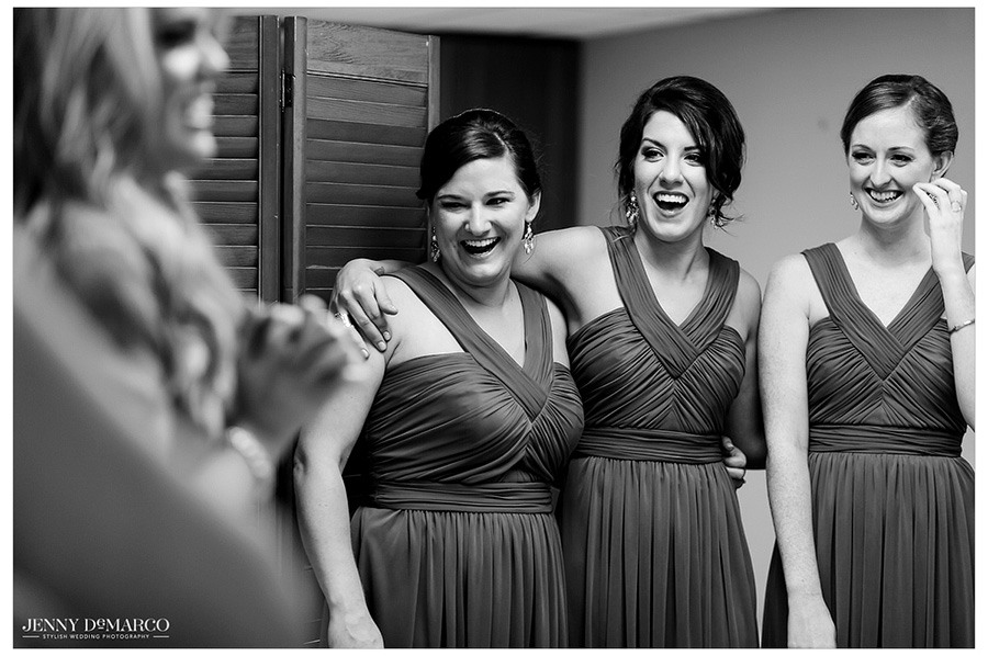 Bridesmaids admire the bride in her wedding gown.