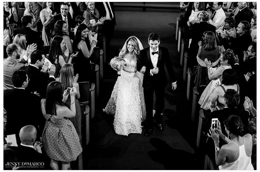 Black and white photo of the bride and groom walking down the aisle.
