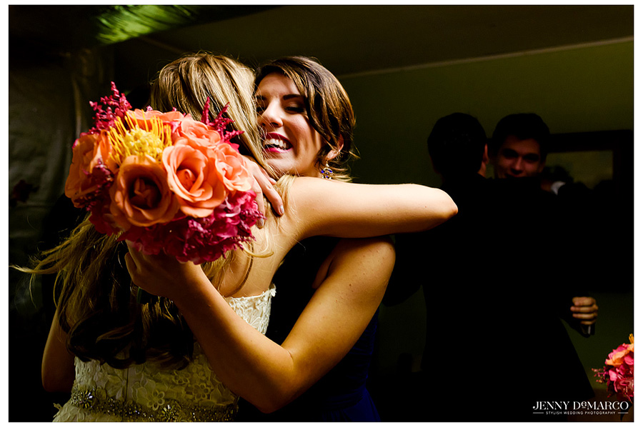 Photo of the bride and one of her bridesmaids hugging.