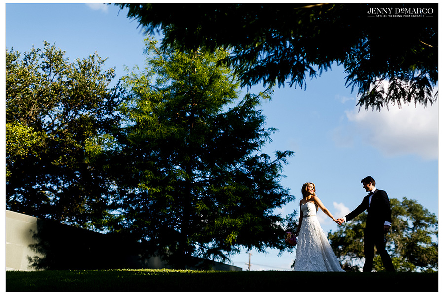 Photo of the bride and groom in the shade of tall trees outside the reception venue.