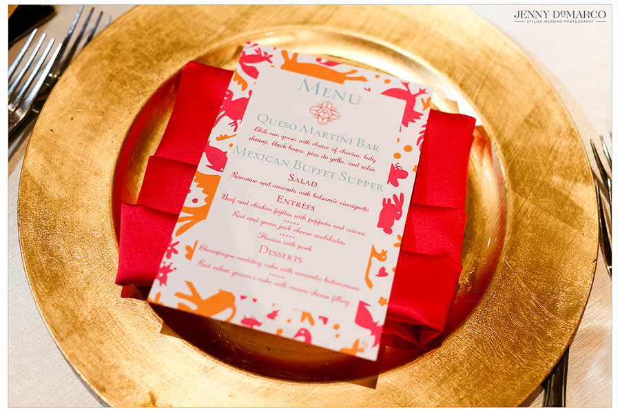 Photo of the bright pink and orange menu card , displayed on a gold plate. The wedding decor was bright and floral fiesta-inspired, with gold accents.