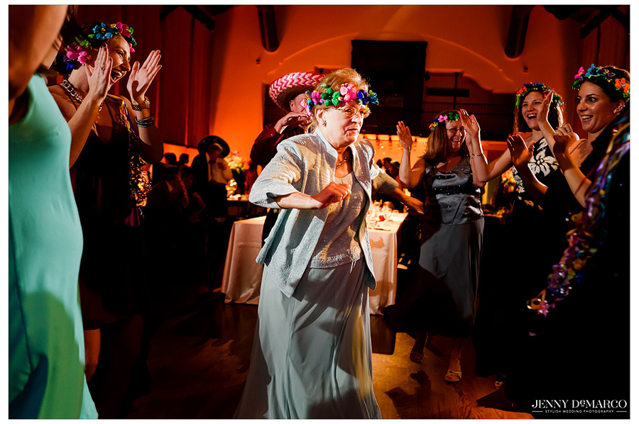 Grandmother, wearing a festive floral hair wreath, dancing at the wedding reception.