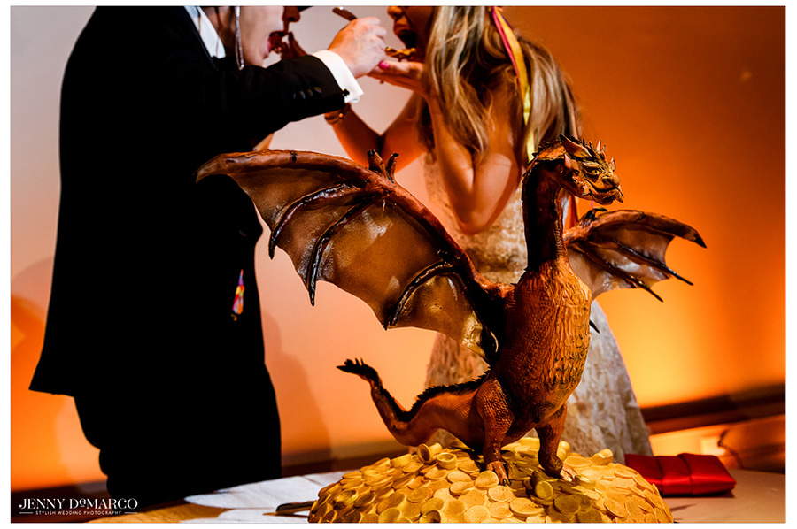 The bride and groom feed each other cake at the reception. The cake was 'Game of Thrones' themed, with a miniature dragon topper.