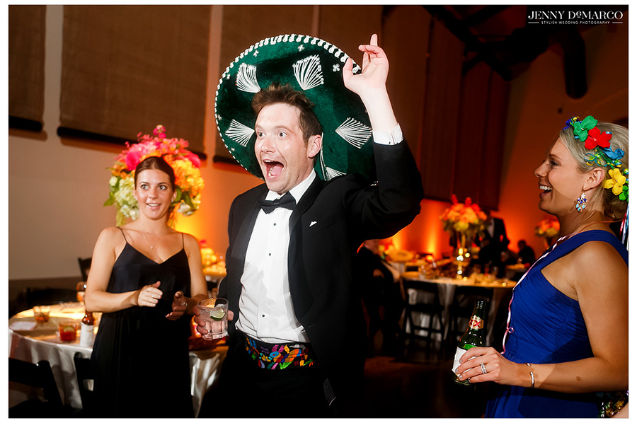 Wedding guests laugh and dance, wearing floral wreaths and sombreros at the wedding reception.