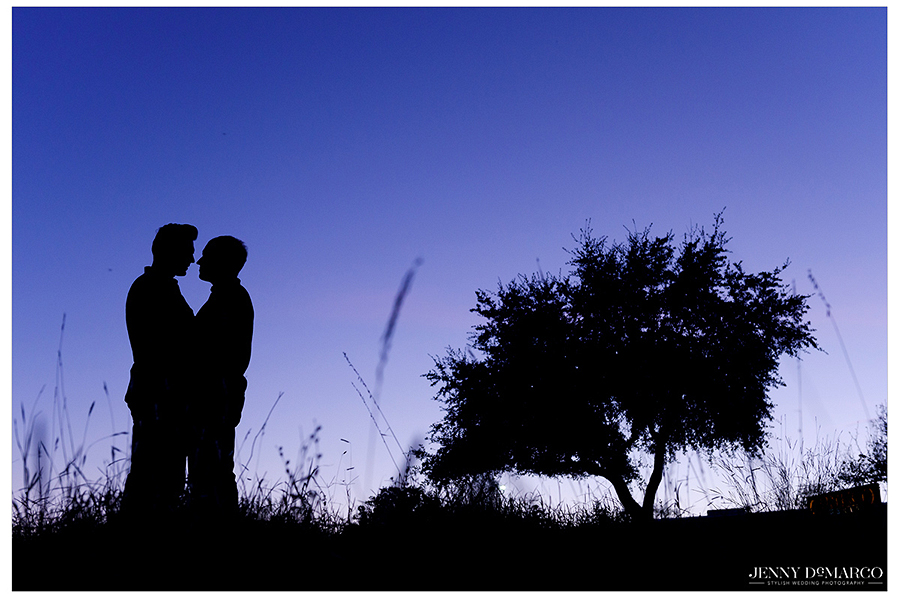 Silhouette of gay couple kissing at sunset
