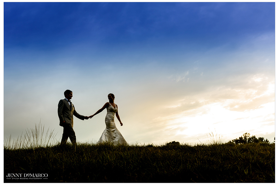 Bride and groom walking outdoors at sunset.