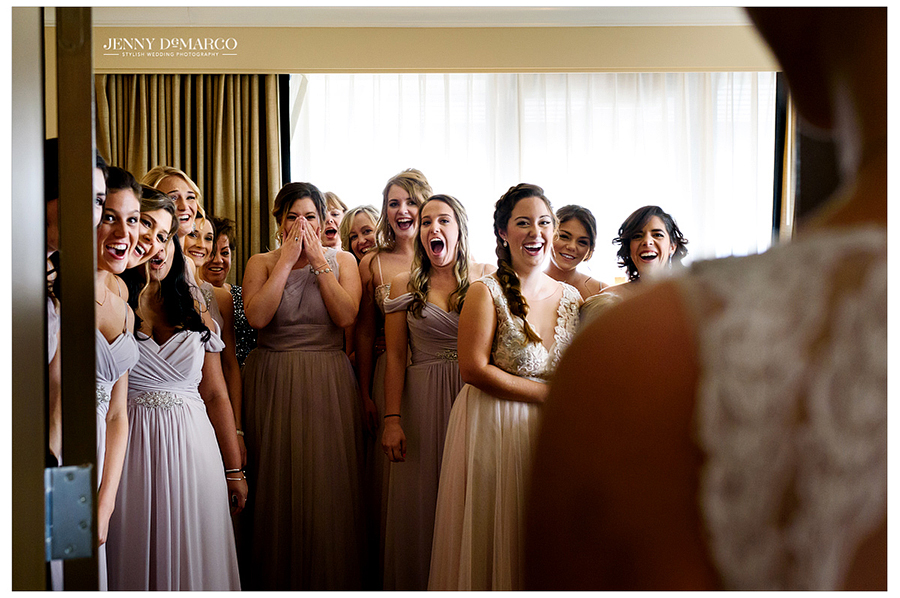 Photo of bridesmaids excitedly seeing the bride in her dress for the first time.