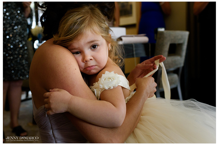 Pouting flower girl gets a cuddle from her mother.