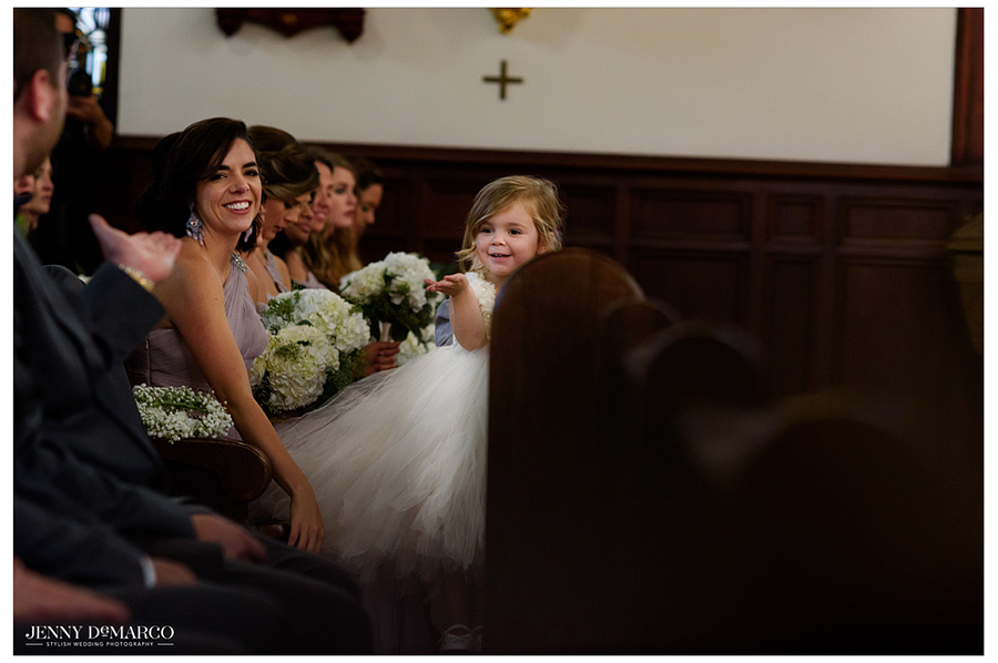 Flower girl smiles from the pew.