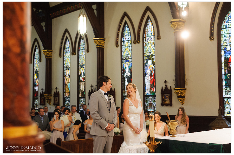 The bride and groom stand together facing the altar during the wedding ceremony.