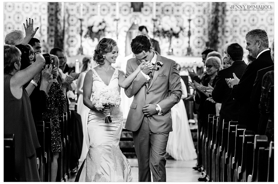 Black and white photo of the groom kissing the bride's hand as they exit the church together at the end of the ceremony.