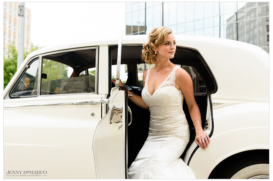 Photo of the bride getting in to a classic white car.