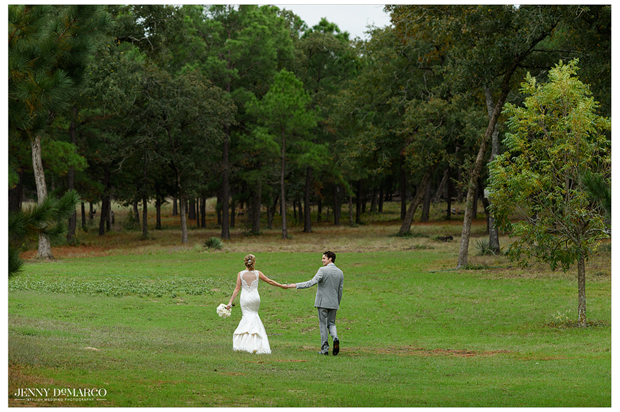 Photo of the bride and groom together in a field surrounded by trees.