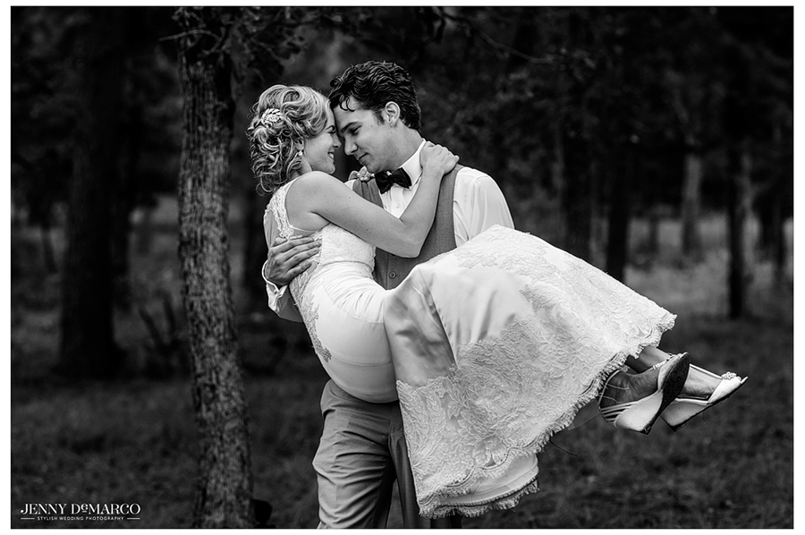 Black and white photo of the groom picking up the bride outdoors, surrounded by trees.