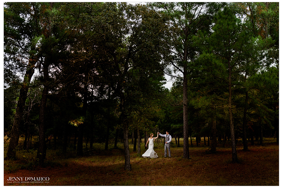 Photo of the bride and groom outdoors in a clearing surrounded by trees.