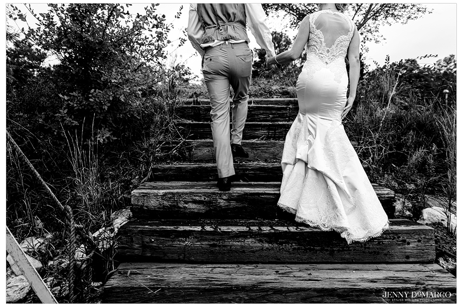 Black and white photo of the bride and groom climbing rough-hewn wooden steps outdoors.