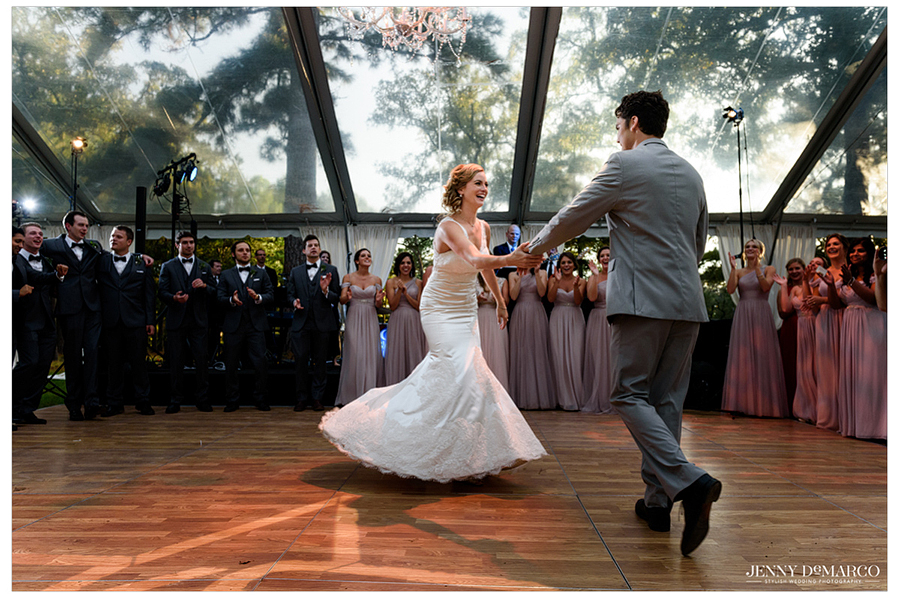Photo of the bride and groom twirling together during their first dance.