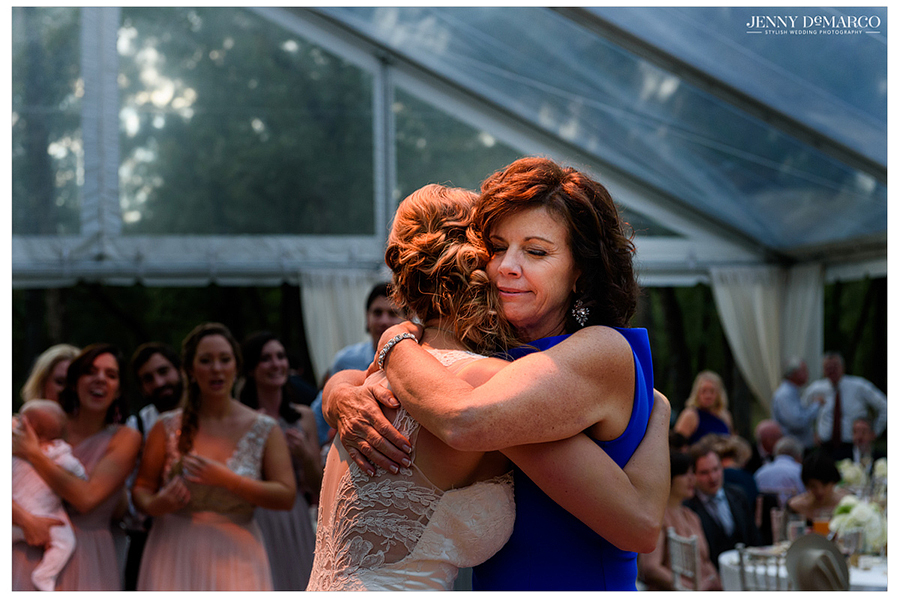 Photo of the bride and her mother hugging at the beginning of the wedding reception.