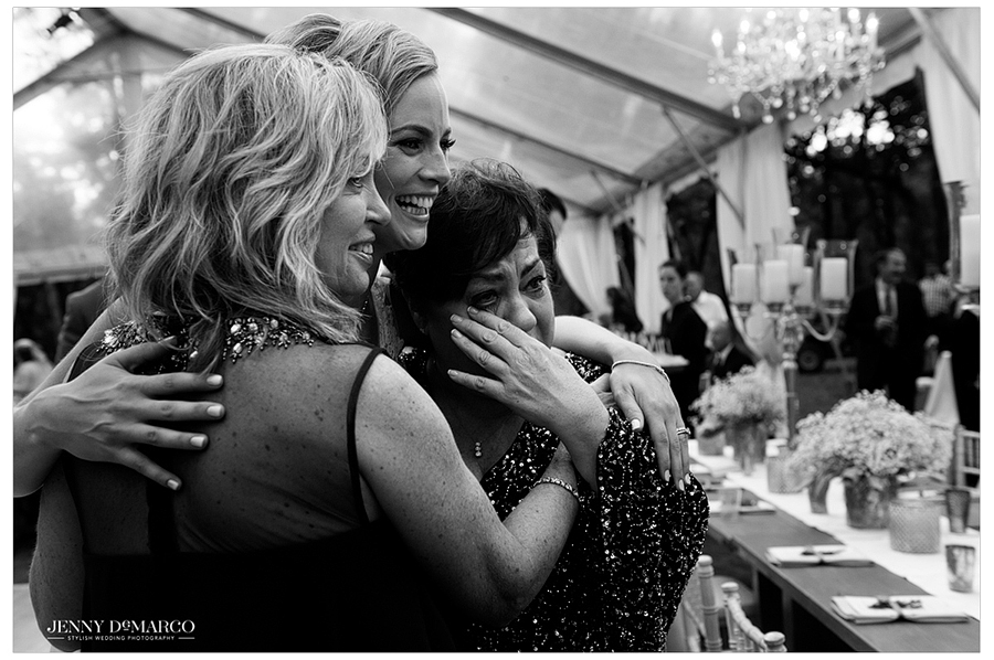 The bride poses for a photo with her happy, tearful aunts during the wedding reception.
